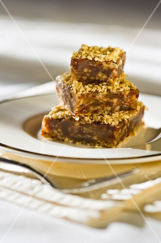 A stack of date and ginger slices with sesame seeds