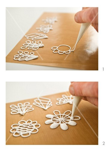 White chocolate flowers being pipped onto baking paper