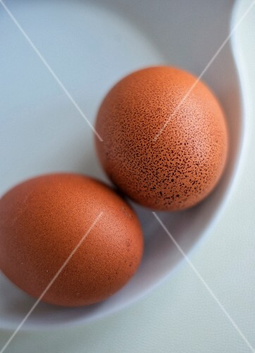 Two brown eggs in a bowl