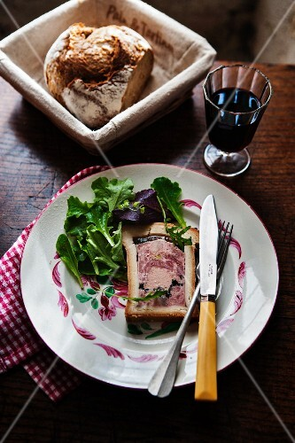 Pâté en croute with a mixed leaf salad, bread and red wine