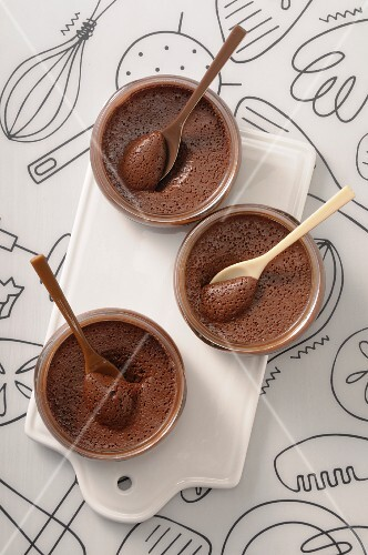 Three bowls of chocolate mousse with spoons
