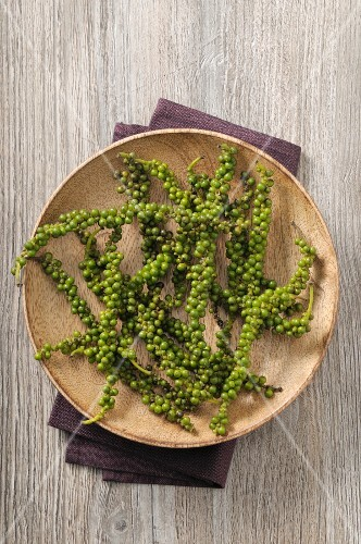 Green pepper vines on a wooden plate