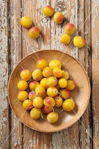 Yellow plums on a wooden plate and next to it