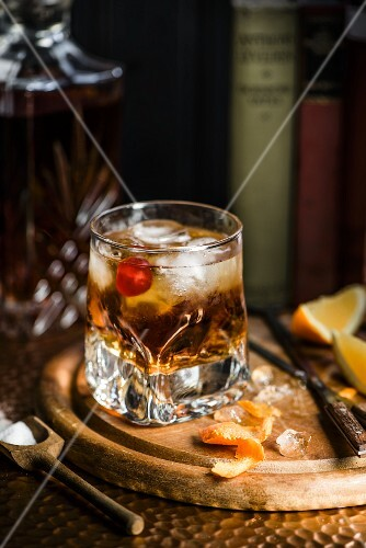A whisky garnished with a cocktail and orange