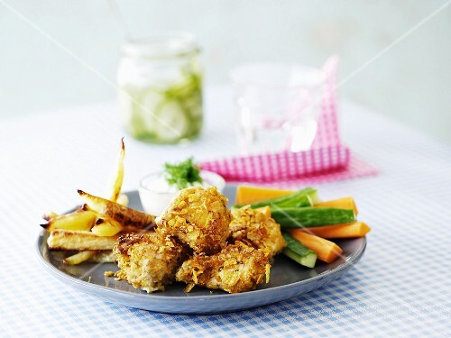 Chicken in a cornflakes coating with chips, vegetable sticks and cucumber yoghurt