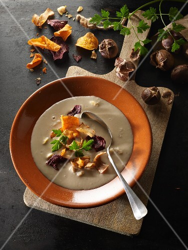 Cream of chestnut soup with vegetables chips and parsley