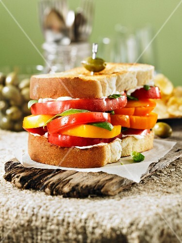 A giant sandwich with red and yellow tomatoes