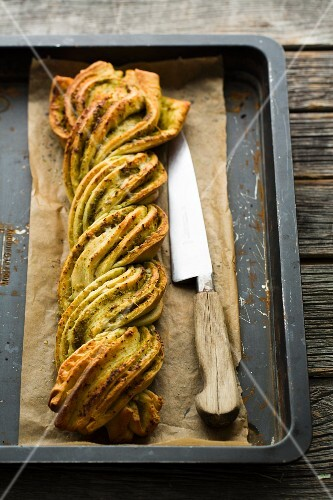 A plaited pesto loaf on a baking tray with a knife