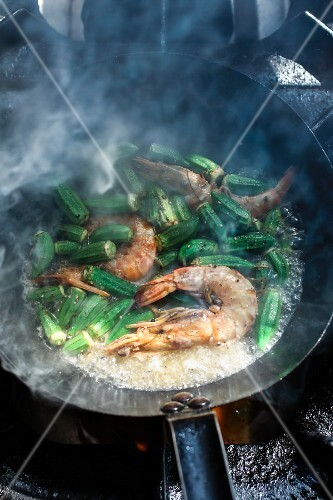 Prawns with okra pods being fried in a pan in a kitchen at the Machane-Jehuda market, Jerusalem