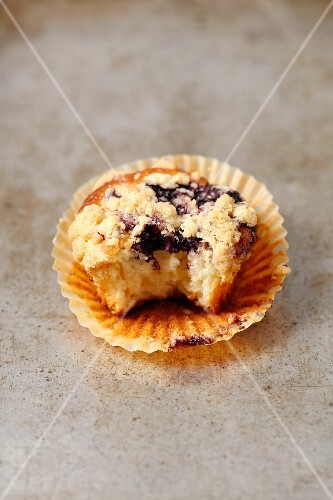 A yoghurt cupcake with blueberries and crumbles with a bite taken out