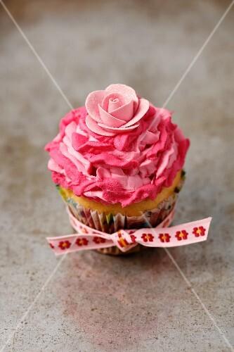 A vanilla cupcake with pink mascarpone cream and a decorative flower