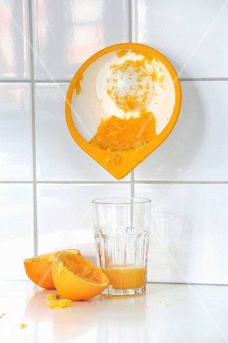 A wall-mounted citrus press and a glass of freshly squeezed orange juice