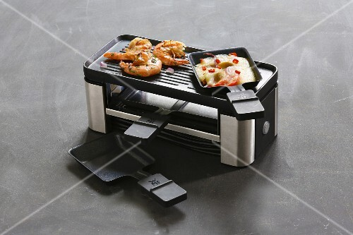 A raclette for two pans with a grill