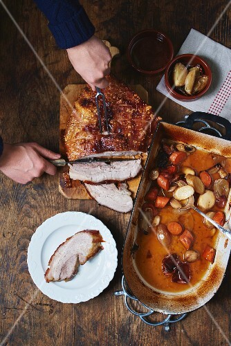 Crispy roast pork and root vegetables in a roasting tin