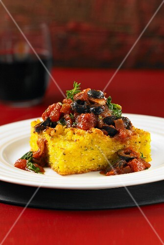 Polenta cake with olive and tomato and spinach