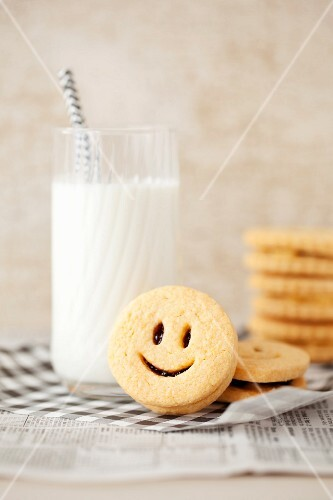 Smiley jam sandwich biscuits with a glass of milk