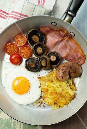 A full English breakfast with a fried egg, bacon, hash browns, mushrooms and tomatoes