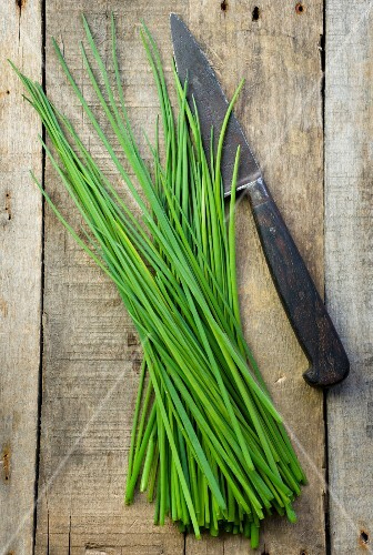 Fresh chives with a knife on a wooden surface