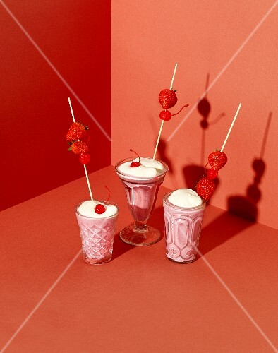 A strawberry milkshake with cream and cocktail cherries
