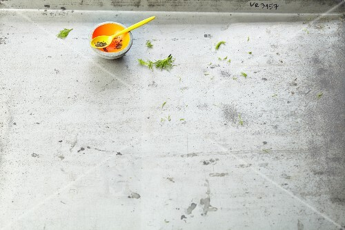 A bowl with a spoon on a grey surface