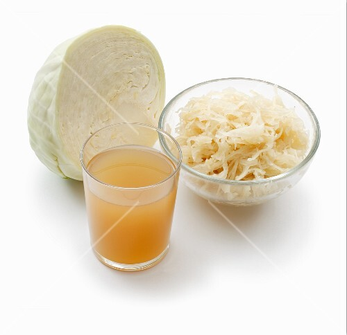White cabbage, sauerkraut and a glass of sauerkraut juice on a white surface