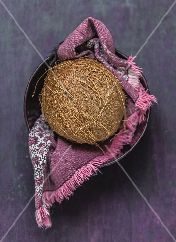 A coconut on a cloth in a bowl