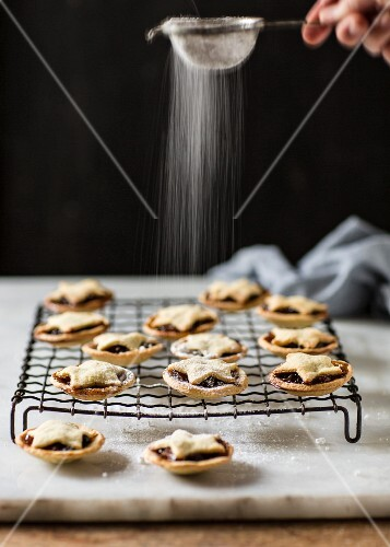 Mince pies on a cooling rack being dusted icing sugar
