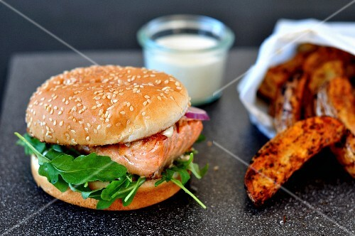 A salmon burger with potato wedges