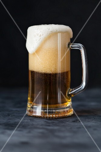 A glass of beer with overflowing foam
