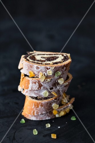 A stack of poppy seed roll cake slices with icing, dried fruit and nuts (Poland)