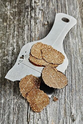 Summer or burgundy truffles (Tuber blotii) sliced on a truffle slicer