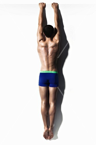 Muscular young man wearing blue shorts hanging from white wall
