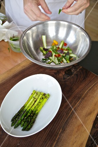 A chef making a salad in a stainless steel bowl
