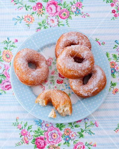Sugared doughnuts on a floral-patterned plate