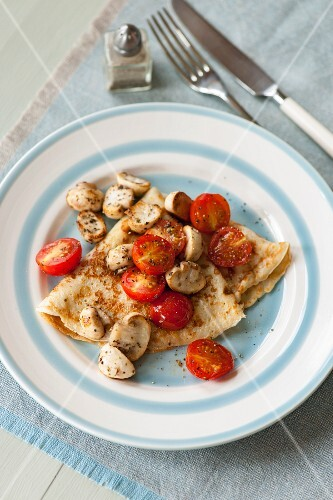 Pancakes with cherry tomatoes and mushrooms