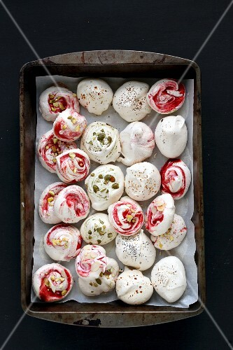 Meringues with strawberry swirls, cardamom, poppy seeds, chopped pistachios and pumpkin seeds