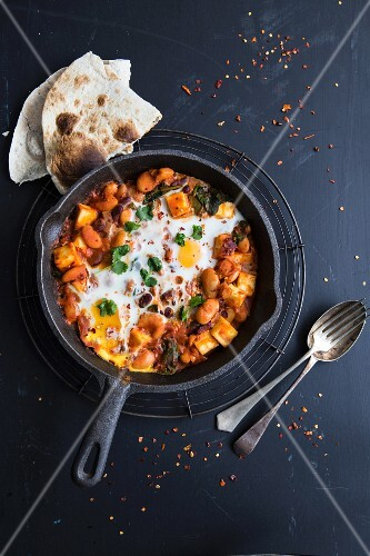 Vegetable curry with fried eggs and unleavened bread (India)
