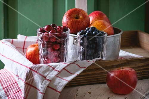 An aluminium bowl of red apples and glasses of blackberries and lingonberries on an old white wooden chair against the green wooden walled