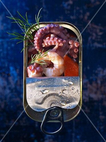 Seafood (squid, king prawns and surimi) in a tin with dill (seen from above)