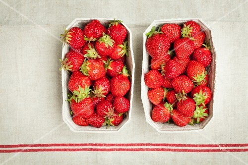 Two paper punnets of fresh strawberries (seen from above)