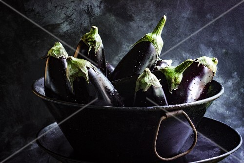 Fresh aubergines in a metal bowl