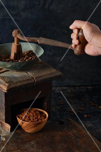 Coffee beans being ground in an antique wooden grinder