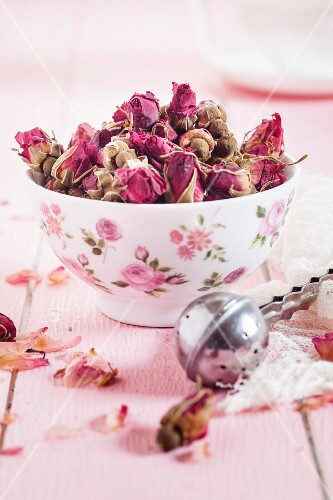 Bowl of dried Moroccan rosebuds and tea infuser for making rose tea