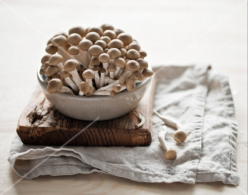 Fresh shimeji mushrooms in a ceramic bowl on a chopping board