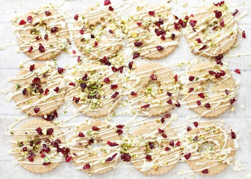 Ring biscuits decorated with white chocolate, cranberries and pistachio nuts