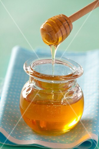Honey dripping from a honey spoon in a jar