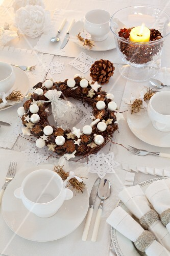 Table festively set in white with wreath of pine cone and baubles