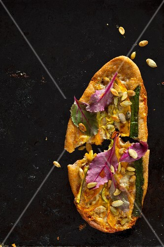 Pizza with courgettes, pumpkin, pumpkin seeds, goat's cheese and beetroot leaves