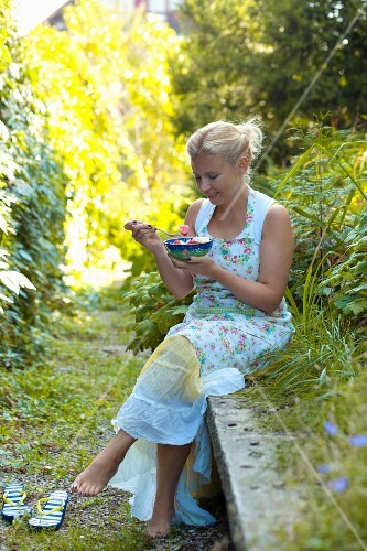 A woman eating tomato salad with feta cheese in a garden
