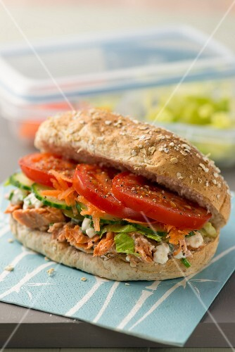 A wholemeal roll with salmon salad and tomatoes